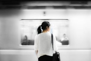 woman watching blurred shape of a subway train pass by