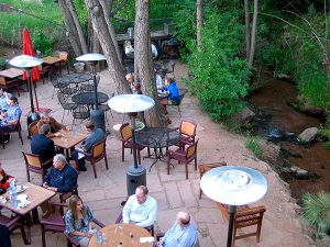people enjoying a meal next to a creek