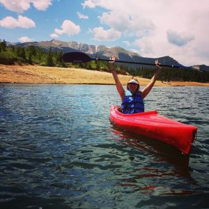 Lady in a red kayak with Pikes Peak in background